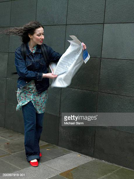 Young woman on street holding map blowing in wind