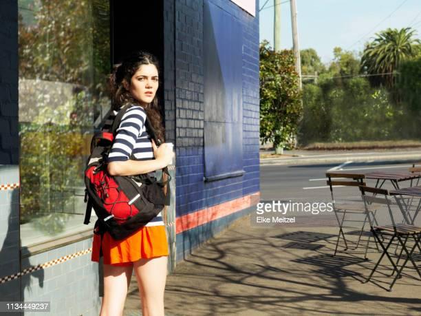 young woman on street looking over her shoulder - mulher saia curta imagens e fotografias de stock