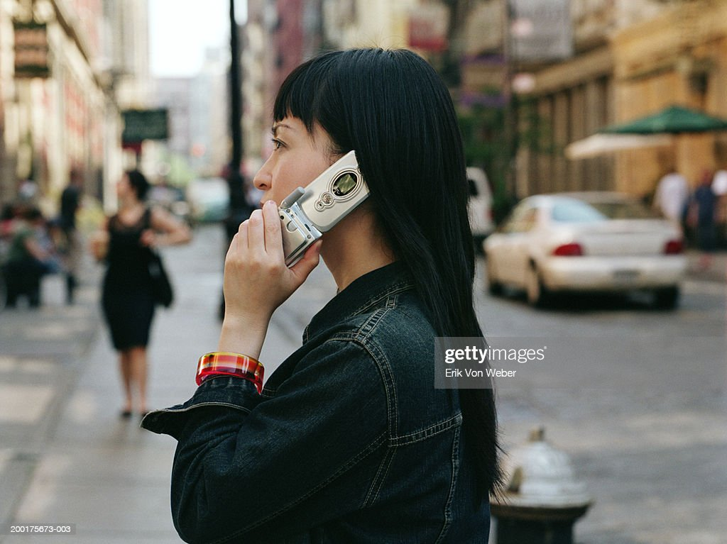 Young woman on street using mobile phone, side view : Stock Photo