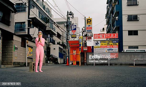 Young woman on street wearing pink alien costume, pointing gun