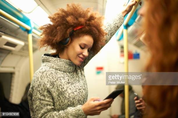 young woman on subway train, looking at smartphone - parapetto barriera foto e immagini stock