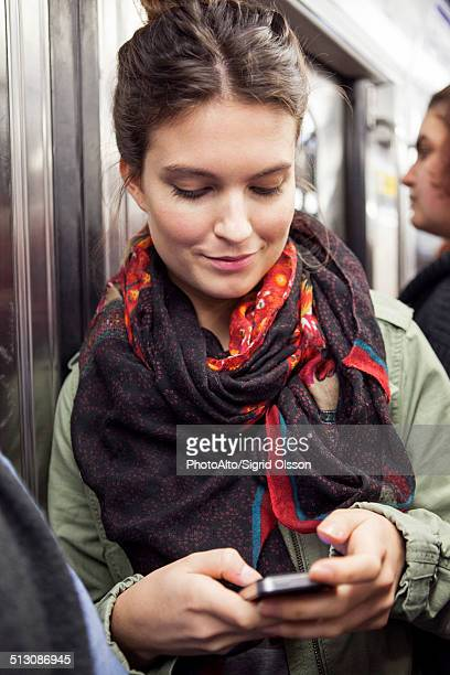 Young woman on subway using smartphone