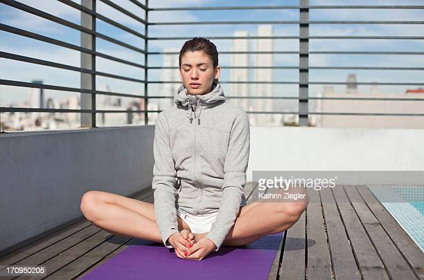 young woman on sun deck stretching/exercising - sweatshirt stock pictures, royalty-free photos & images