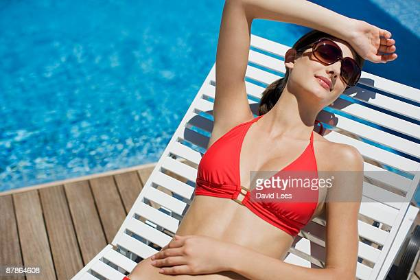 Young woman on sun lounger by swimming pool
