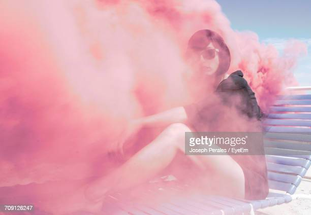 Young Woman On Sun Lounger In Pink Smoke