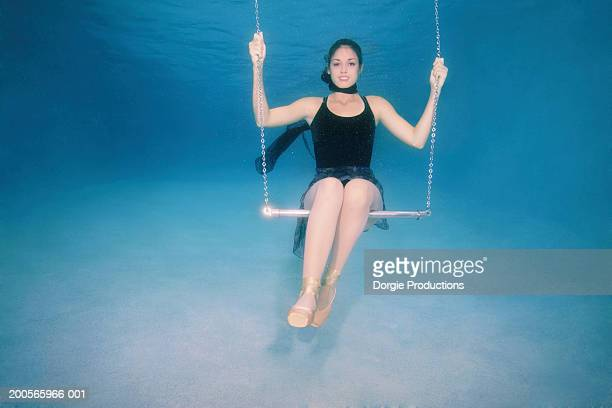 Young woman on swing underwater, portrait