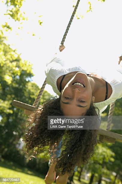 young woman on swing with head upside down - down blouse stock-fotos und bilder