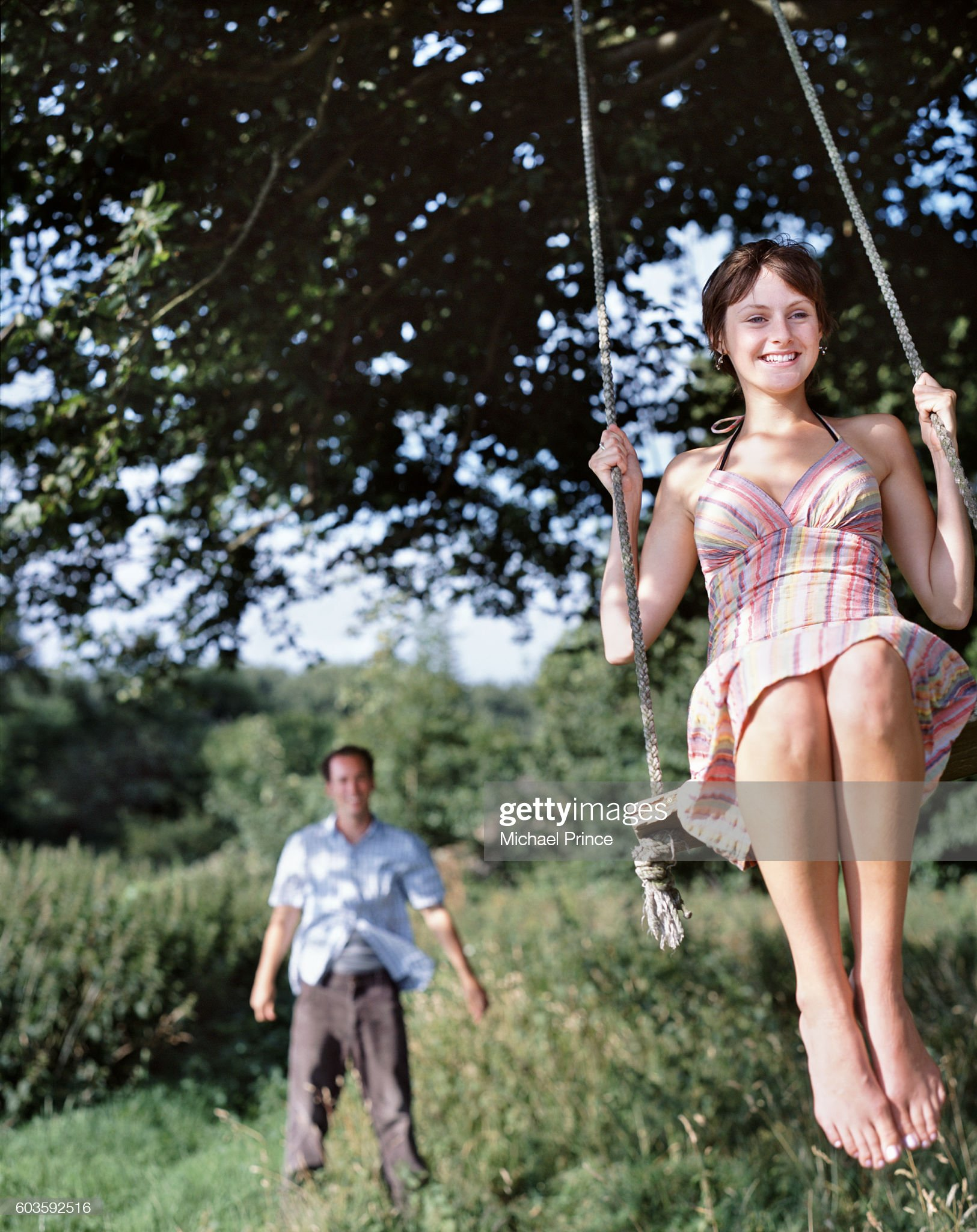 https://media.gettyimages.com/photos/young-woman-on-swing-with-man-watching-picture-id603592516?s=2048x2048