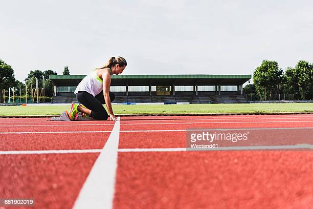 Young woman on tartan track in starting position