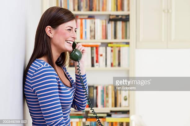 Young woman on telephone at home, side view