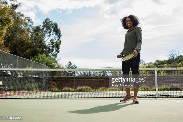 young woman on tennis court - racket sport stockfoto's en -beelden