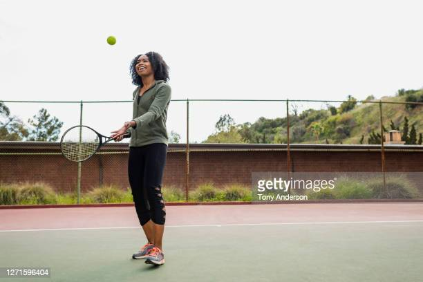 young woman on tennis court - tennis stock pictures, royalty-free photos & images