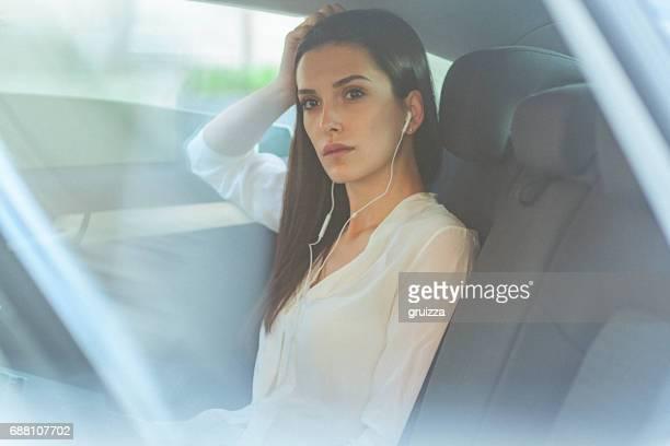 ポッド キャストを聴くイヤホンを使用して車の後部座席に若い女性