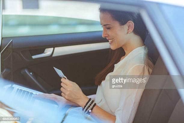 Jeune femme sur la banquette arrière d'une voiture, à l'aide de sa carte de crédit et un ordinateur portable pour une transaction en ligne