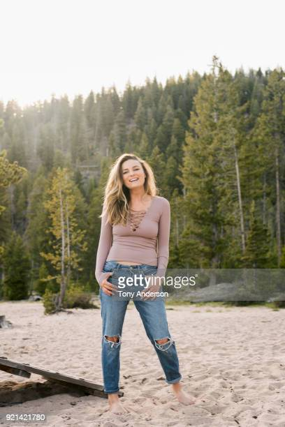 young woman on the beach at mountain lake - beige pants stock pictures, royalty-free photos & images