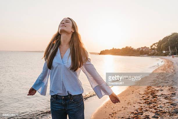Young woman on the beach at sunset