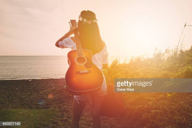 young woman on the beach carrying a guitar at sunset - hippie woman stock photos and pictures