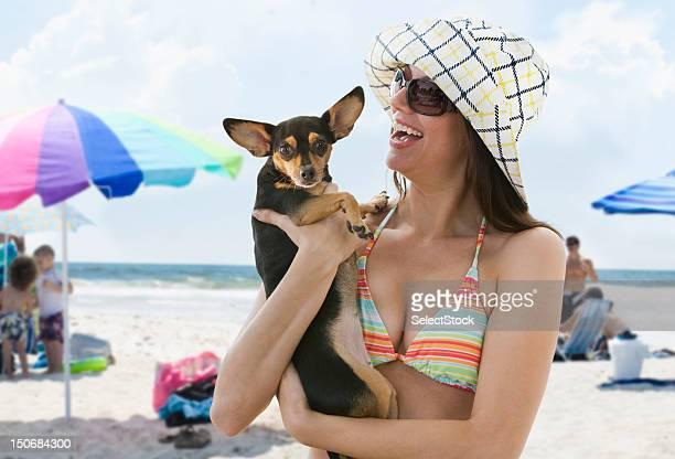 Jeune femme sur la plage, tenant un petit chien