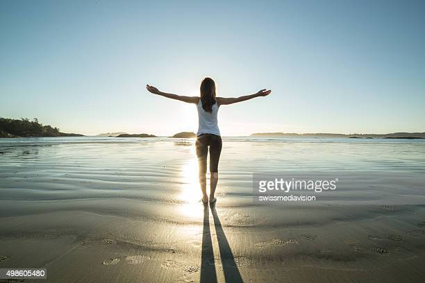 Young woman on the beach in autumn arms outstretched