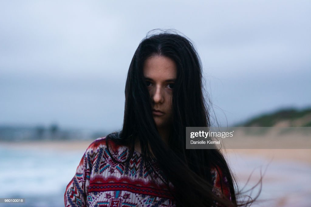 Young woman on the beach in evening, front view : Stock-Foto