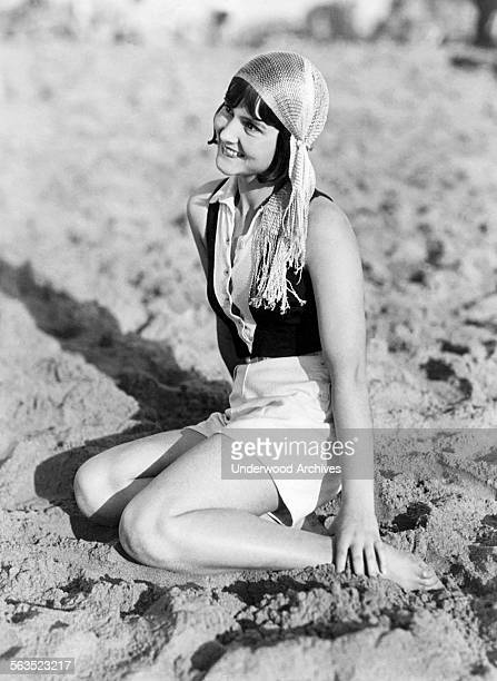 Young woman on the beach in Venice wearing the latest in modish headwear, the 'Gypsy cap,' which is made of a silk like netting, Los Angeles,...