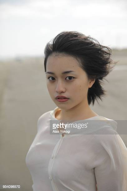 a young woman on the beach - ショートヘア ストックフォトと画像