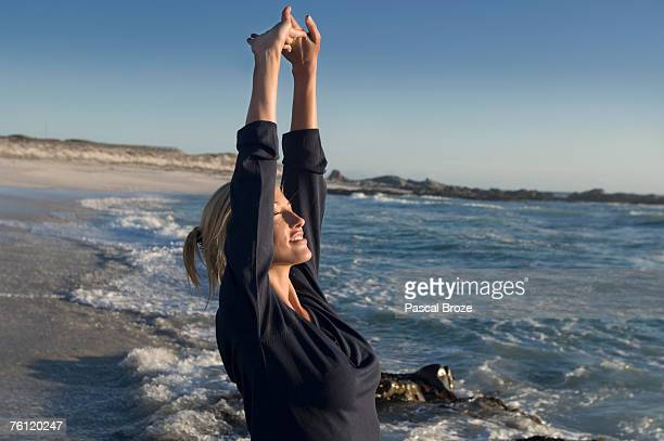 Young woman on the beach, stretching, outdoors