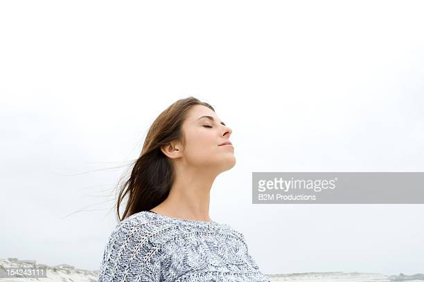 A young woman on the beach with closed eyes