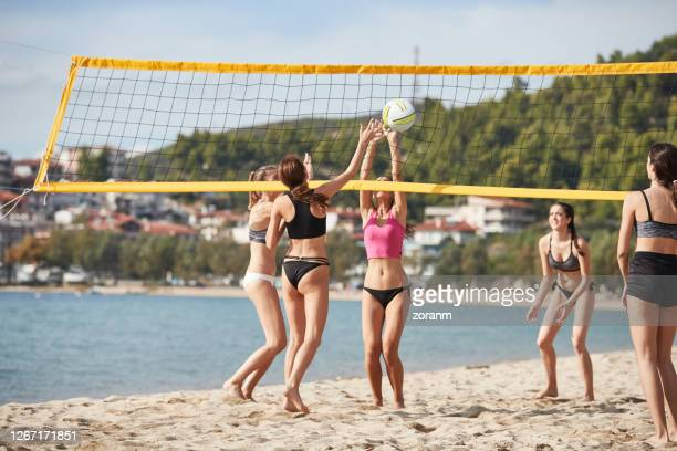 young woman on the beach with friends pushing the volleyball into the net - beach volley foto e immagini stock