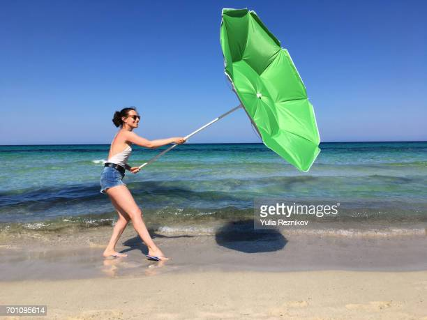 Young woman on the beach with umbrella at the windy day