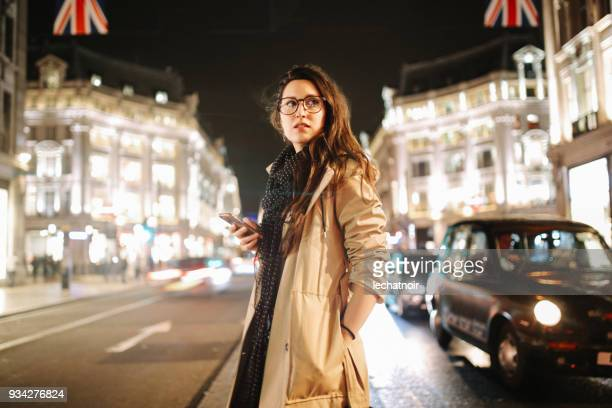 young woman on the busy streets of london downtown in the evening, texting on the cellphone - female streaking stock pictures, royalty-free photos & images