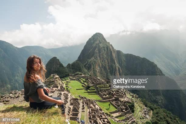 young woman on the cliff in the ancient city of machu picchu, peru. - peru stock-fotos und bilder