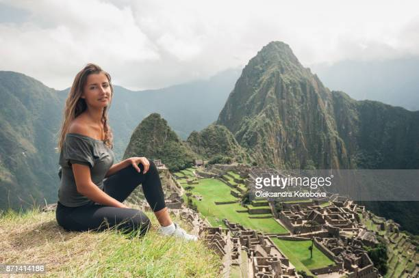 Young woman on the cliff in the ancient city of Machu Picchu, Peru.