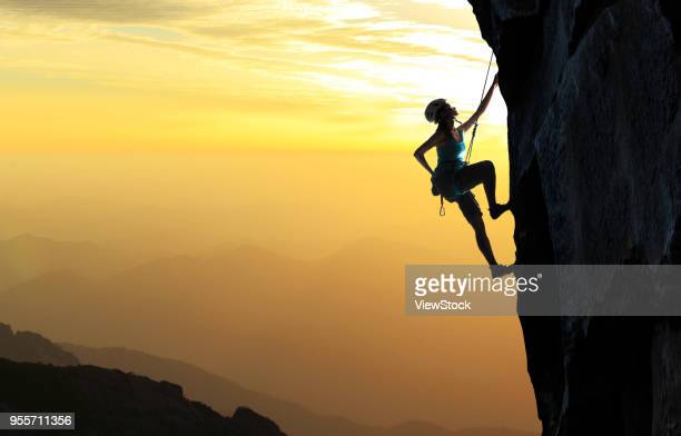 young woman on the cliff rock climbing - スクランブリング ストックフォトと画像