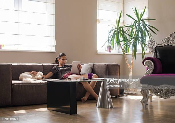 Young woman on the couch with her dog looking at tablet