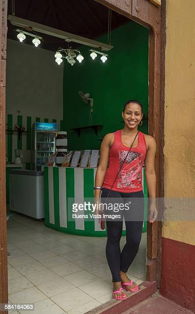 Young woman on the door of her shop