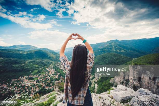 Young woman on the mountain top showing heart-shaped symbol