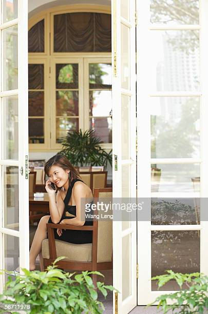 Young woman on the phone, view through open doors