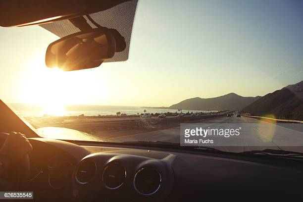 young woman on the road driving pacific coast highway at sunset, california, usa - landfahrzeug stock-fotos und bilder