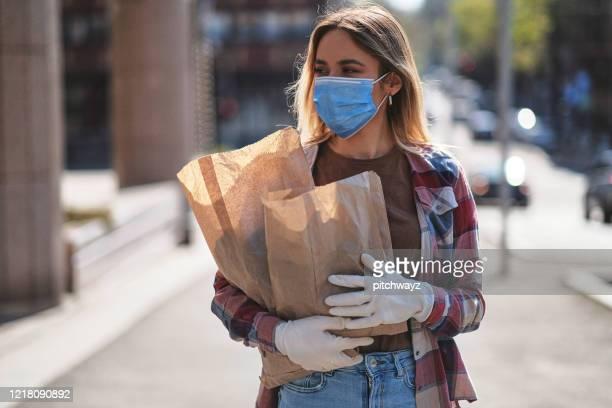 young woman on the street, during covid-19 pandemic - máscara cirúrgica imagens e fotografias de stock