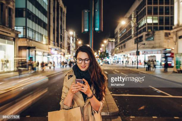 young woman on the streets of london downtown in the evening calling a cab - mid adult stock pictures, royalty-free photos & images