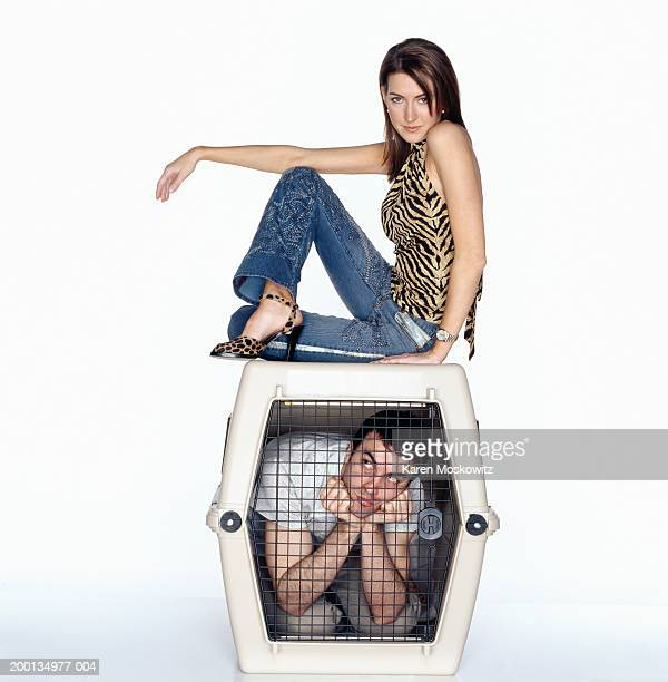 Young woman on top of dog cage containing man, portrait