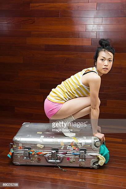 Young woman on top of suitcase