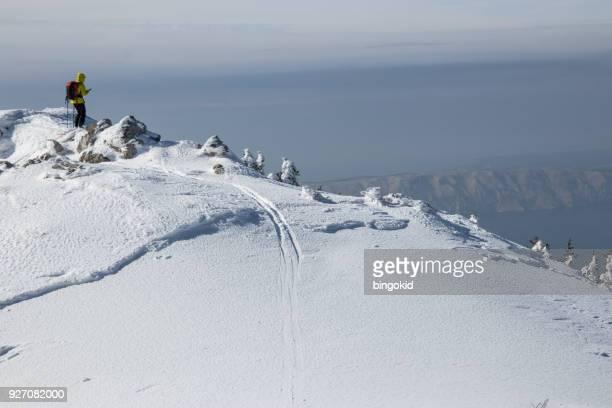 Junge Frau auf dem Schnee Berg mit Meer bedeckt