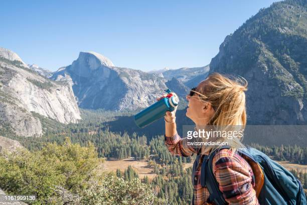 young woman on top of yosemite valley, usa drinking water from reusable bottle - reusable stock pictures, royalty-free photos & images