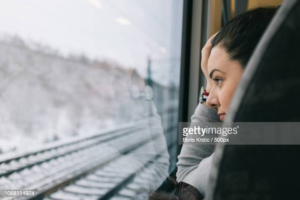 young woman on train looking through window - bahngleis stock-fotos und bilder