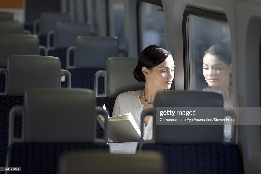 Young woman on train reading a book : Stock Photo