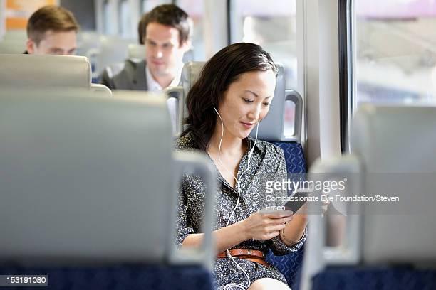 young woman on train using mobile phone - fahrzeug innenansicht stock-fotos und bilder