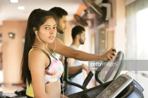 Young woman on treadmill at gym