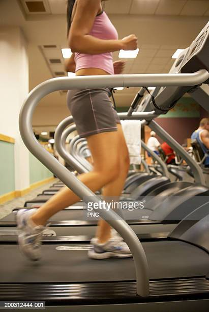 Young woman on treadmill, side view, low section (blurred motion)